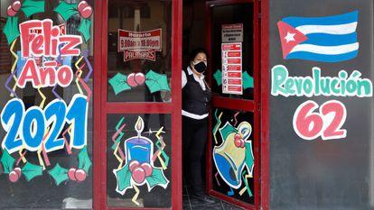 Uma mulher à porta de um bar em Havana, Cuba.