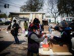 AME8262. BUENOS AIRES (ARGENTINA), 30/09/2020.- Una mujer obtiene alimentos hoy en un comedor comunitario, en una villa de la Ciudad de Buenos Aires (Argentina). Argentina difunde este miércoles el porcentaje de la población que en el primer semestre del año estaba bajo la línea de pobreza, una situación que ya en diciembre del año pasado sufría el 35,5 % y que se espera haya aumentado por los efectos de la cuarentena por el coronavirus decretada en marzo, aún vigente. EFE/JUAN IGNACIO RONCORONI
