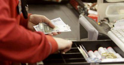 Trabalhadora abre a caixa registradora em supermercado.