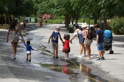 Várias crianças, acompanhadas por adultos, caminham por um riacho em Valência na última quinta-feira.