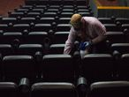 27 January 2021, Venezuela, Caracas: An employee cleans the cinema after the end of a movie. Cinemas and theatres are allowed to reopen in Venezuela. Photo: Pedro Rances Mattey/dpa