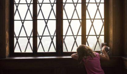 Uma menina espera junto a uma janela.