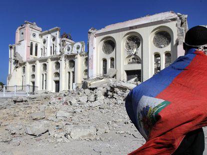 Um homem, coberto pela bandeira haitiana, caminha pelas ruínas da catedral de Porto Príncipe (17/01/2010).