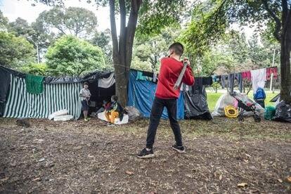 Menino pratica beisebol em um acampamento improvisado por imigrantes venezuelanos, em Bogotá.