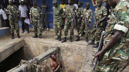 Suposto integrante da milícia juvenil Imbonerakure, do partido governante, suplica a soldados que o protejam de uma multidão de manifestantes em maio de 2015 no Burundi