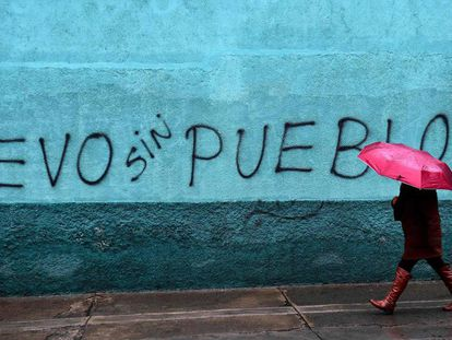 Mulher caminha por um muro em La Paz, Bolívia.