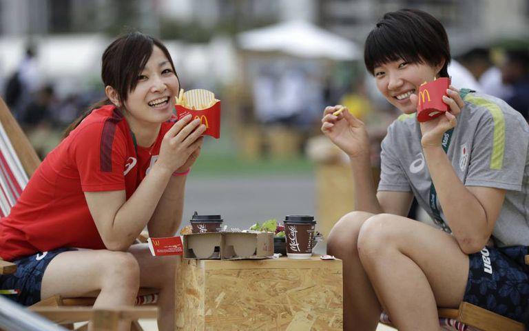 Atletas olímpicas japonesas comem no McDonald's da Vila Olímpica.