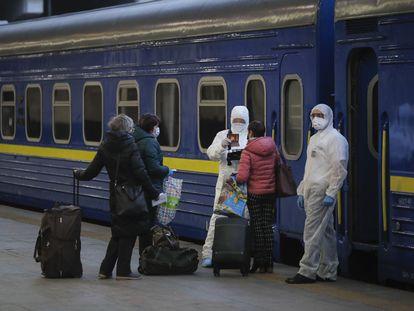 Trabalhadores com macacão de proteção verificam os documentos dos passageiros prestes a embarcar, na estação de Kiev, em um trem para Moscou.