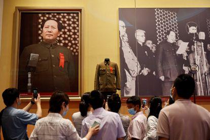 Um grupo de pessoas contempla imagens de Mao Tsé-tung no Museu de História do Partido Comunista da China, em Pequim.
