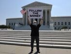 """Bill Christeson holds a sign reading """"follow the money"""" in anticipation of a U.S. Supreme Court ruling on U.S. President Donald Trump's bid to block his financial records from being obtained by third parties, outside the court in Washington, U.S., July 8, 2020. REUTERS/Jonathan Ernst"""