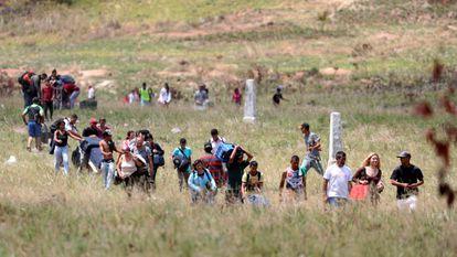 Pessoas tentam cruzar a fronteira entre Brasil e Venezuela na cidade de Pacaraima, Roraima.