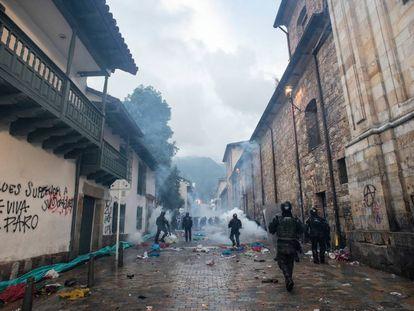 Membros do Esquadrão Móvel Antimotim lançam gases e caminham pelos escombros após os confrontos na Plaza Bolívar, em 21 de novembro de 2019.