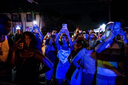 Pessoas gravam com seus celulares a implosão do edifício.