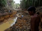 A Yanomami indian follows agents of Brazil's environmental agency in a gold mine during an operation against illegal gold mining on indigenous land, in the heart of the Amazon rainforest, in Roraima state, Brazil April 17, 2016. Picture taken April 17, 2016. REUTERS/Bruno Kelly