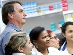FILE PHOTO: Brazil's President Jair Bolsonaro poses for pictures with employees of a drugstore, amid the coronavirus disease (COVID-19) outbreak, in Brasilia, Brazil, April 10, 2020. REUTERS/Adriano Machado/File Photo