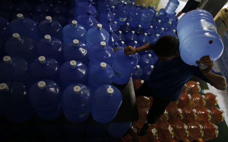 Com demanda em alta, funcionário de mercado organiza galões de água.