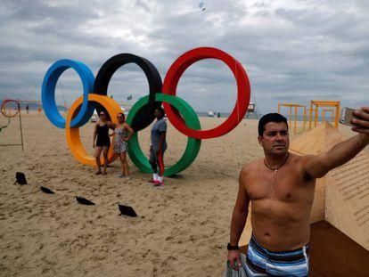 Homem faz um selfie em frente ao símbolo das Olimpíadas em Copacabana.