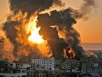 A fire rages at sunrise in Khan Yunish following an Israeli airstrike on targets in the southern Gaza strip, early on May 12, 2021. - Israeli air raids in the Gaza Strip have hit the homes of high-ranking members of the Hamas militant group, the military said Wednesday, with the territory's police headquarters also targeted. (Photo by YOUSSEF MASSOUD / AFP)