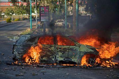 Carro da polícia israelense em chamas depois de uma manifestação contra a ofensiva de Israel, na terça-feira na cidade de Lod, ao sul de Tel Aviv.