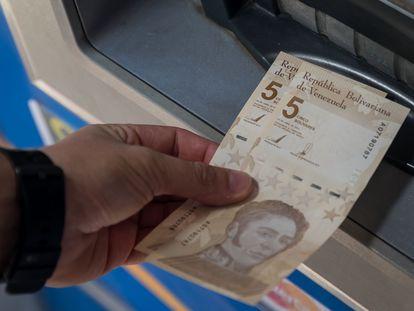 Uma pessoa saca duas notas de 5 bolívares digitais, a nova moeda venezuelana, nesta sexta-feira em Caracas.