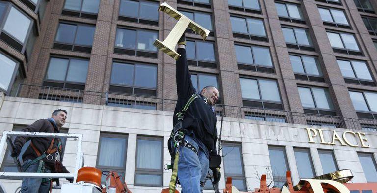 Um funcionário retira as letras do complexo Trump Place.
