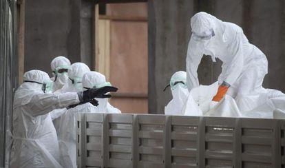 Enfermeiras na Libéria preparam corpos de vítimas do ebola.