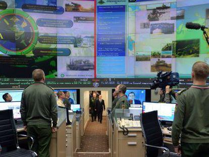 Ao fundo, o presidente russo, Vladimir Putin, durante uma reunião militar.