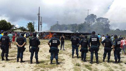 Policiais vigiam o local onde manifestantes queimaram acampamento em que dormiam imigrantes venezuelanos em Paracaima (Roraima).
