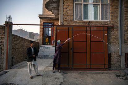 Uma família se despede em 1º de junho, em Cabul, daqueles que partem, jogando água para que seu caminho seja luminoso e voltem logo.