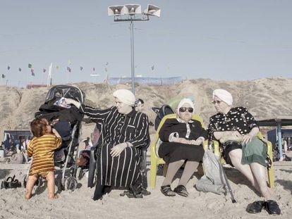 A roupa impede entrar na água, por isso a maioria fica conversando à beira-mar.