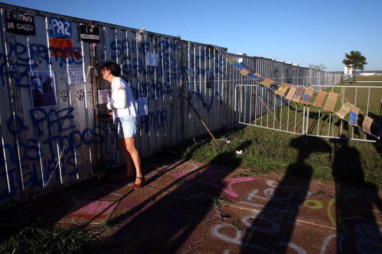 Uma mulher olha a través do muro instalado em Brasília.