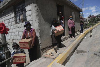 Moradores de Quito carregam cestas básicas recebidas do Governo, em 27 de maio.