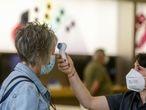 Una trabajadora le toma la temperatura a una clienta en un centro comercial de Madrid.