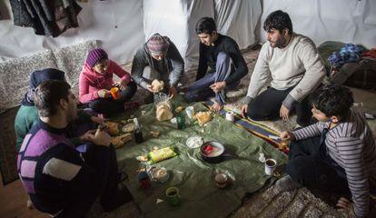 A família yazidi de Arash Faramarzi almoça em sua loja.