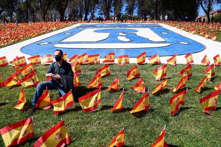 Um homem em parque de Madri onde foram instaladas 53.000 bandeiras da Espanha em respeito às vítimas da covid-19.