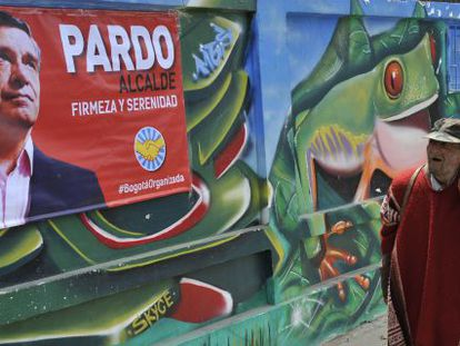 Transeunte passa por cartaz do candidato Rafael Pardo, em Bogotá.
