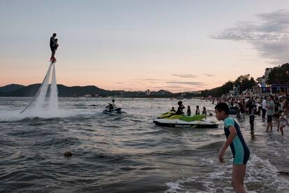 Banhistas se aglomeram para assistir um homem utilizar Jet Ski na praia de Dapeng Jiaochangwei.