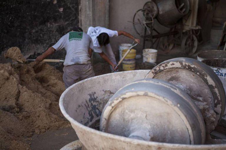 Operários da construção civil preparam mistura de areia e cimento.