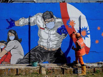 Homem pinta muro com campanha de combate à covid-19 em Jacarta, em 27 de agosto.