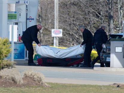Pessoal sanitário remove um cadáver em um posto de gasolina de Enfield, na Nova Escócia, no domingo.