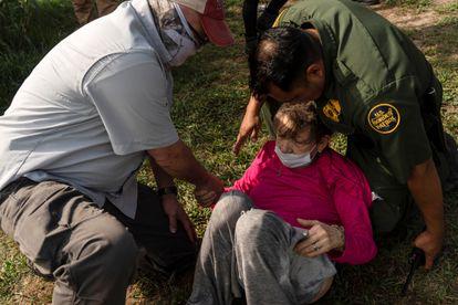 Um agente da patrulha fronteiriça dos EUA auxilia a idosa venezuelana na localidade texana de Del Rio, na quarta-feira.