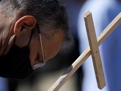Em Belo Horizonte, manifestante leva uma cruz em protesto pelas mortes pela covid-19 no Brasil.