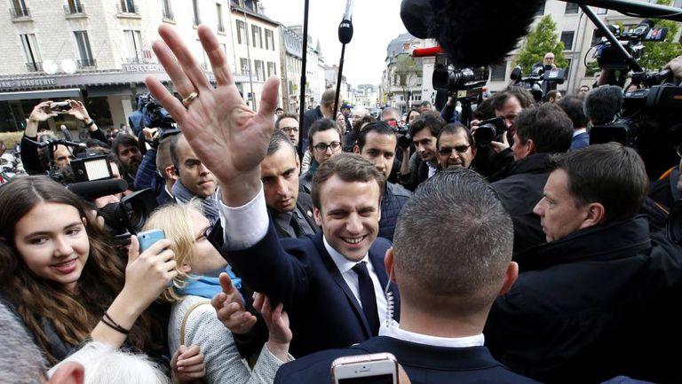 Emmanuel Macron saúda simpatizantes durante evento.