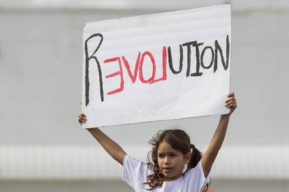 Menina segura cartaz na Marcha das Mulheres de 21 de janeiro.