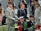 France's President Emmanuel Macron and French Armies Chief Staff General Francois Lecointre stand in the command car as they review troops before the start of the Bastille Day military parade honouring French health workers and their dedication in the fight against the coronavirus disease (COVID-19), in Paris, France July 14, 2020. Christophe Ena/Pool via REUTERS
