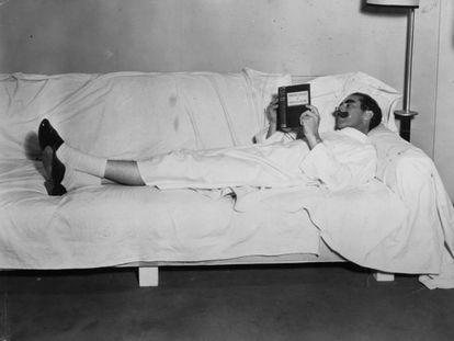 O comediante Groucho Marx lendo durante descanso da gravação do filme 'Diabo a Quatro'.