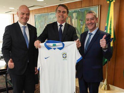 Bolsonaro entre o presidente da FIFA, Gianni Infantino, e o presidente da CBF, Rogério Caboclo, em 2019.