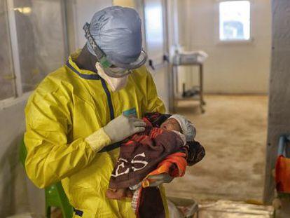 Funcionário do MSF carrega Nubia em seus braços