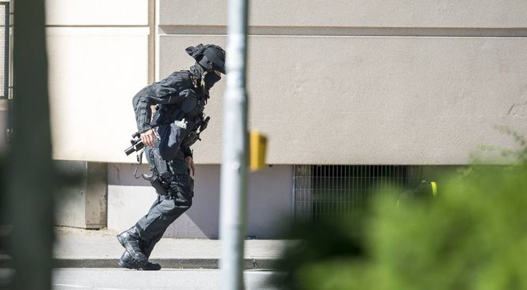 Agente da polícia entra no cinema onde houve tiroteio.