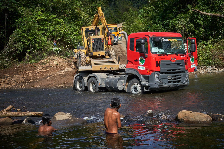 As crianças indígenas Shuar, da comunidade Kawa, observam os caminhões carregando uma escavadeira para trabalhar na nova estrada.
